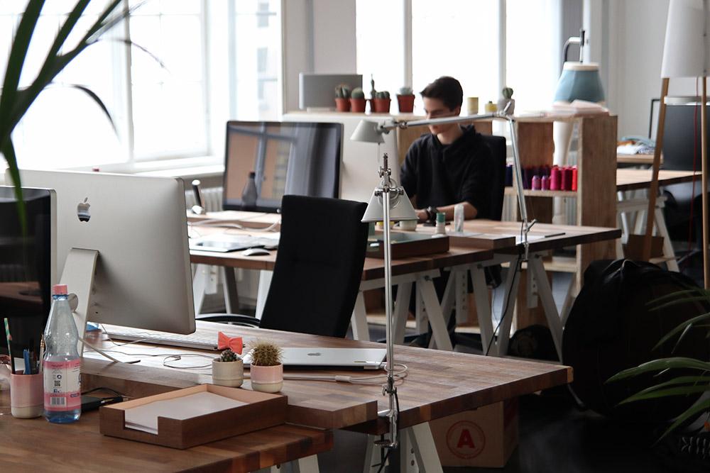 jeune homme travaillant sur ordinateur dans un open space